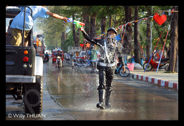 Splashing cop with water in Thai Songkrat festival