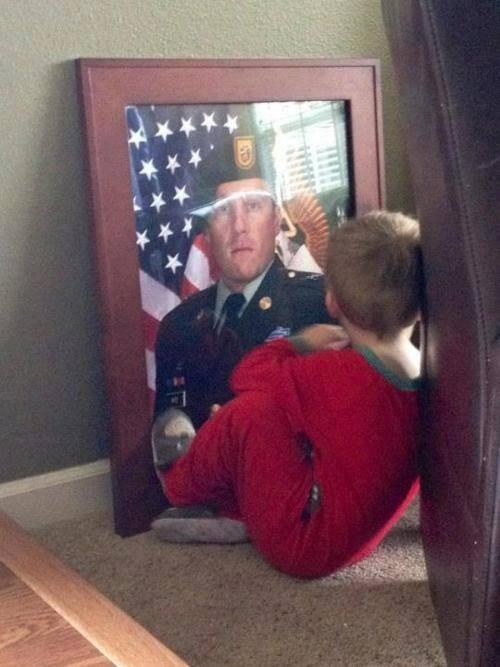 Boy looking at photo of dad killed in action